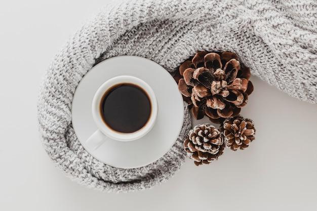 Bovenaanzicht koffiekopje en dennenappels met deken