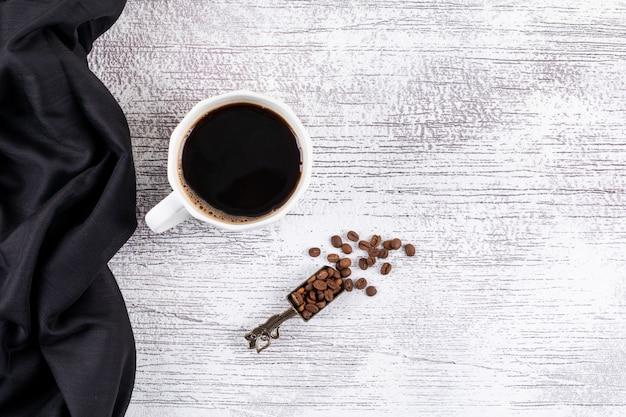 Bovenaanzicht koffiekopje met koffiebonen op witte tafel