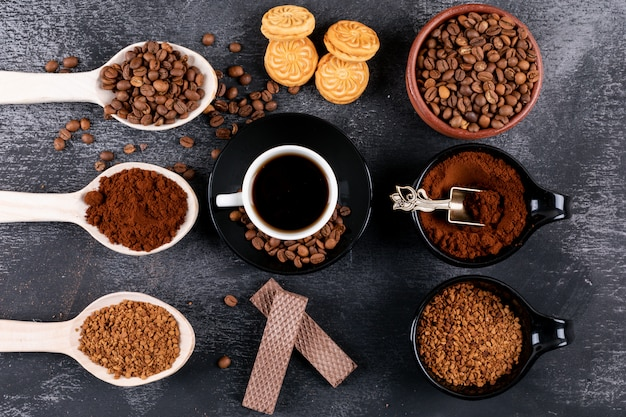 Bovenaanzicht koffiekopje met verschillende soorten koffie op een donkere ondergrond