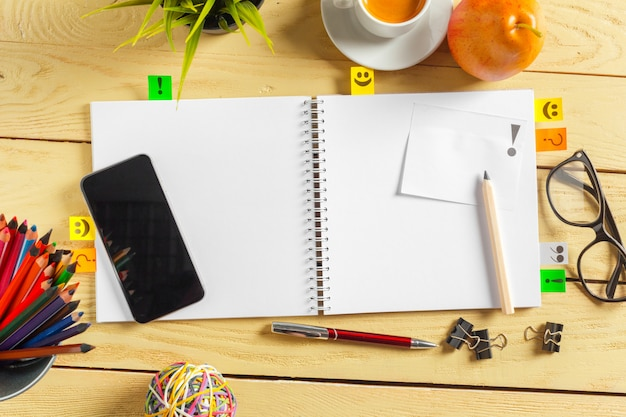 Bovenaanzicht koffiekopje, pen en lege notitieblok op hout