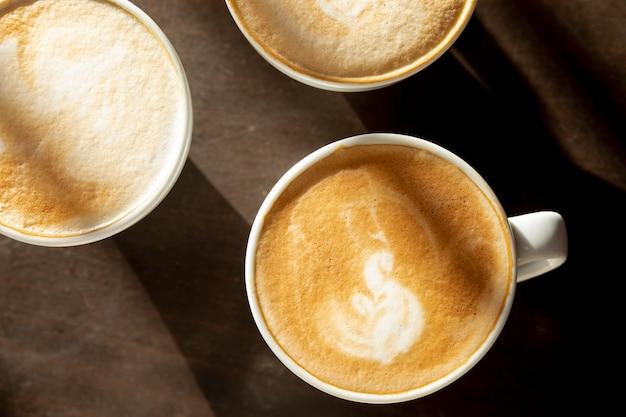 Bovenaanzicht koffiemokken met melk op de tafel