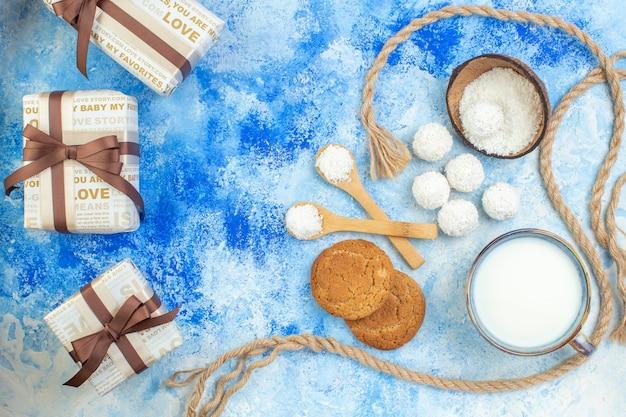 Bovenaanzicht kokos ballen touw houten lepels kopje melk cookies op blauw witte achtergrond
