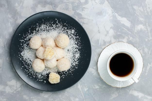 Bovenaanzicht kokos snoepjes met kopje thee op wit