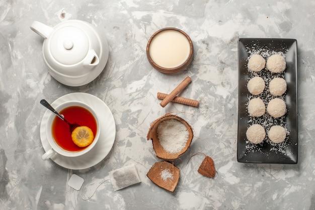 Bovenaanzicht kokos taarten met kopje thee op licht-wit oppervlak