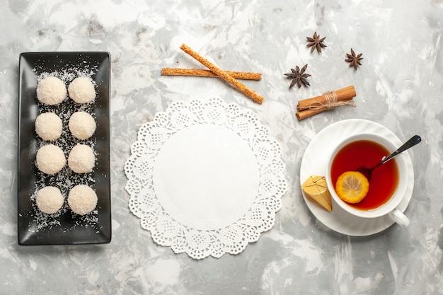 Bovenaanzicht kokos taarten met kopje thee op wit bureau