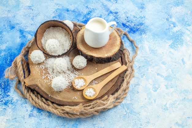 Bovenaanzicht kokosnoot poeder kom kokos ballen houten lepels melk kom op houten plank touw op blauw witte achtergrond