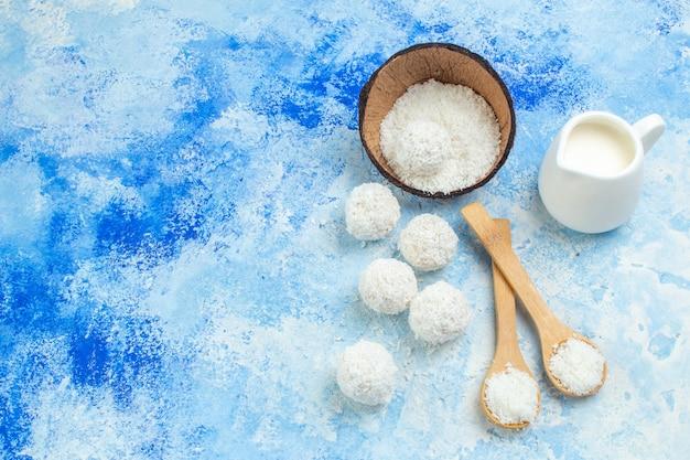 Bovenaanzicht kokosnoot poeder kom kokos ballen touw houten lepels melk kom op blauw witte achtergrond
