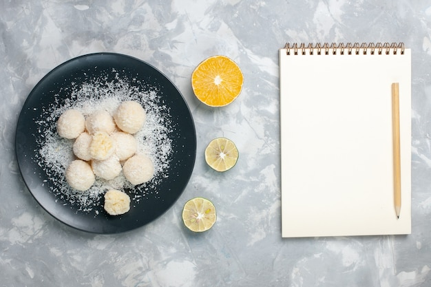 Bovenaanzicht kokosnoot snoepjes met blocnote op lichtwit