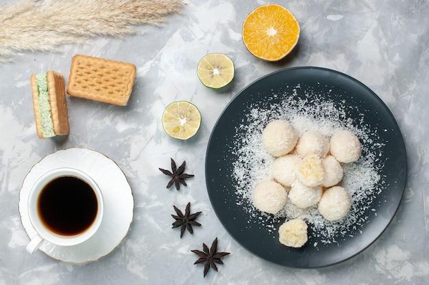 Bovenaanzicht kokosnoot snoepjes met thee op wit