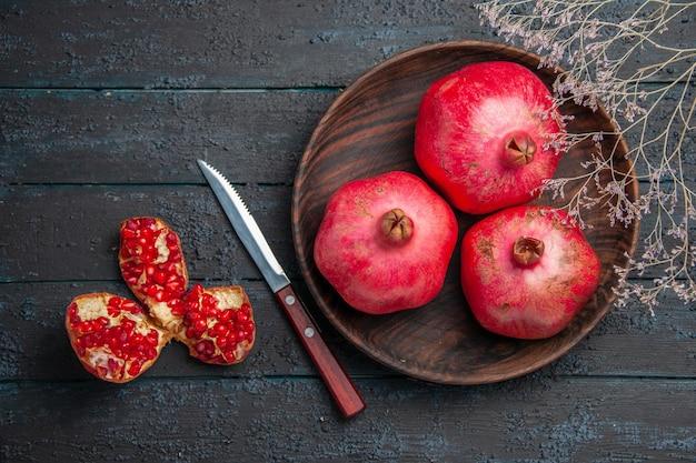 Bovenaanzicht kom granaatappels kom granaatappels naast mes gepilde granaatappel en boomtakken