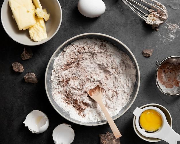 Bovenaanzicht kom met bloem en cacao op de tafel