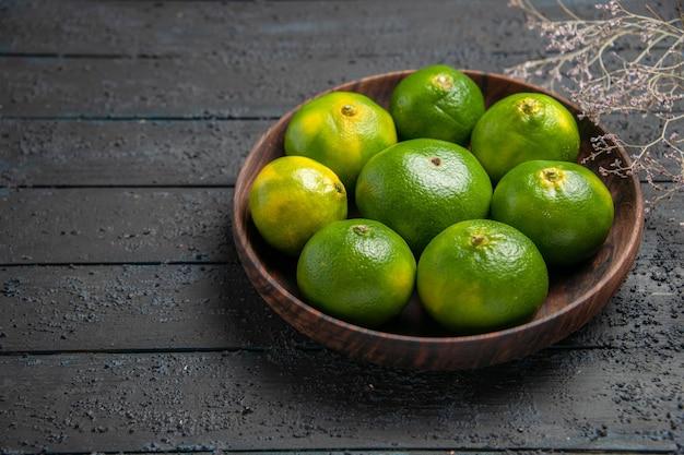 Bovenaanzicht kom met limoenen kom met smakelijke limoenen op grijze tafel