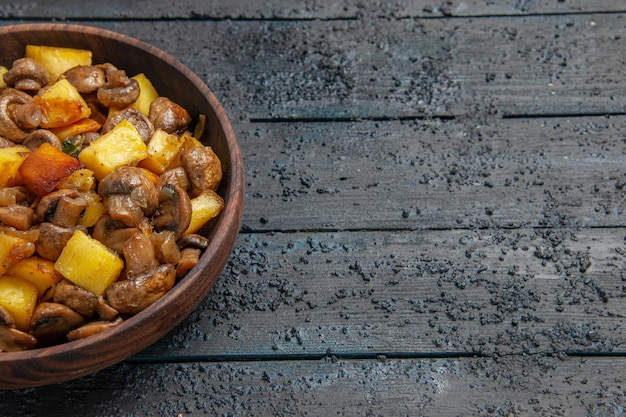 Bovenaanzicht kom met voedsel houten kom met aardappelen en champignons aan de linkerkant van de tafel