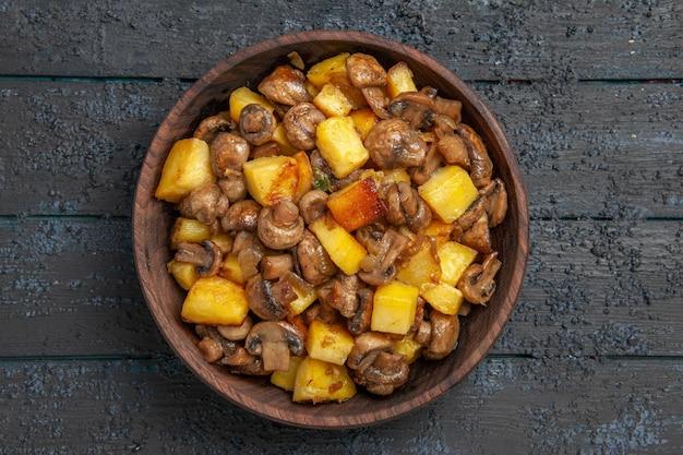 Bovenaanzicht kom met voerbak met aardappelen en champignons op de grijze tafel