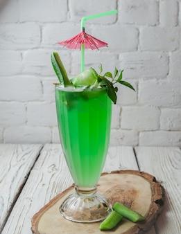 Bovenaanzicht komkommer cocktail met cocktailparaplu en sap stromunt in glazen beker
