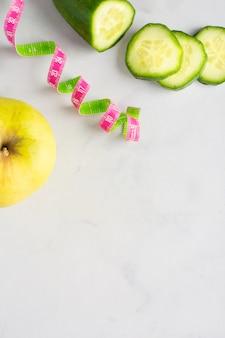 Bovenaanzicht komkommer plakjes en appel met kopie ruimte