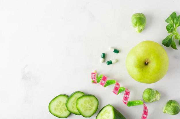 Bovenaanzicht komkommer plakjes met appel en capsules