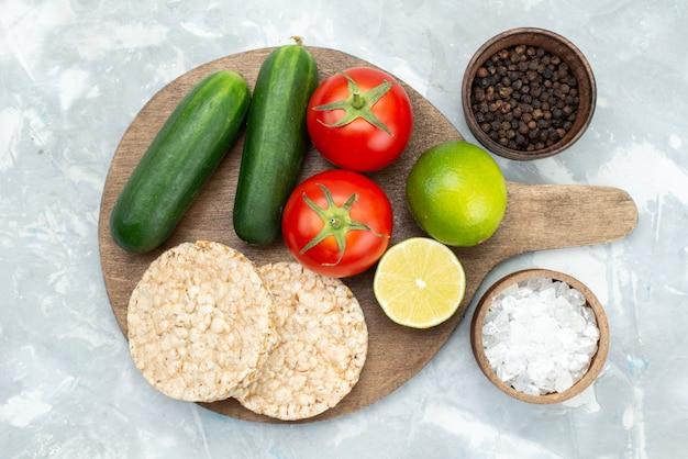 Bovenaanzicht komkommers en tomaten met limoenen en ronde crackers op grijs