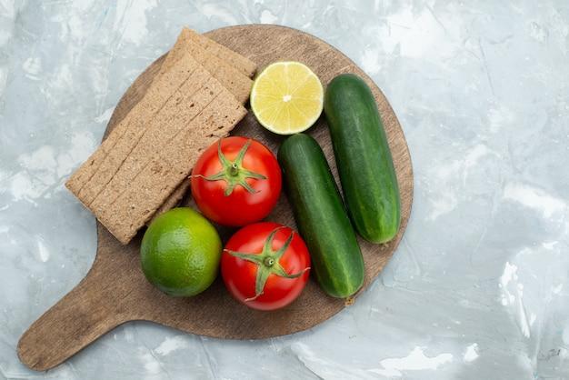 Bovenaanzicht komkommers en tomaten met limoenen (lemmetjes) en chips op grijs