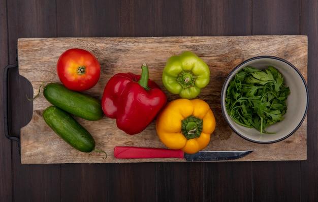 Bovenaanzicht komkommers met paprika op een snijplank met peterselie in een kom op een houten achtergrond