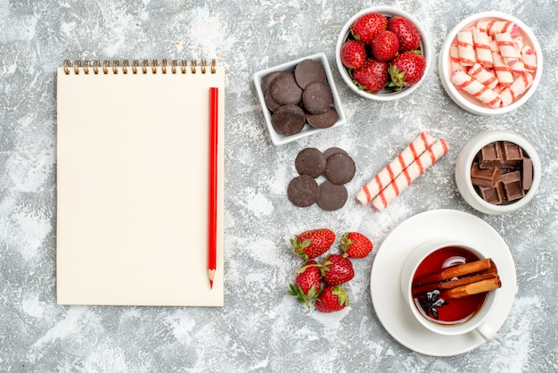 Bovenaanzicht kommen met aardbeien, chocolaatjes, snoepjes en kaneel, anijszaad, thee en notitieboekje met potlood op de grijs-witte grond