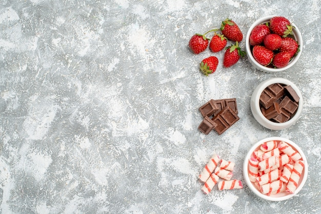 Bovenaanzicht kommen met aardbeienchocolade snoepjes en wat aardbeienchocolade snoepjes aan de rechterkant van de grijswitte grond