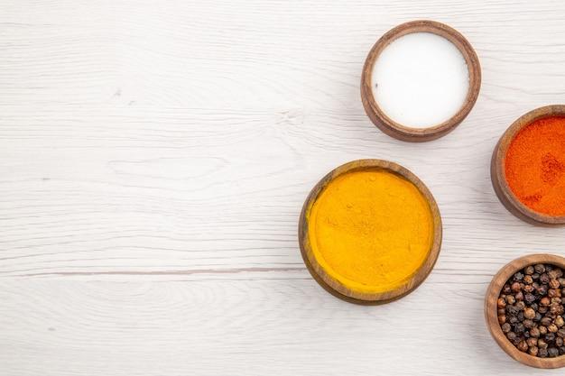 Bovenaanzicht kommen met kruiden kurkuma rode peper poeder zwarte peper zout op grijze achtergrond