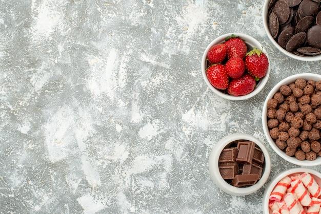 Bovenaanzicht kommen met snoepjes aardbeien bittere en melkachtige chocolaatjes granen en cacao aan de rechterkant van de grijswitte grond