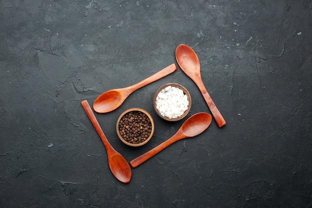 Bovenaanzicht kommen met zeezout en zwarte peper rond houten lepels op donkere tafel met kopie plaats
