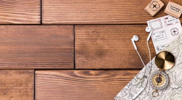 Bovenaanzicht kompas met wereldkaart en oortelefoons