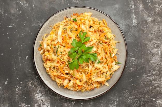 Bovenaanzicht kool de smakelijke kool met wortelen en kruiden op de grijze tafel