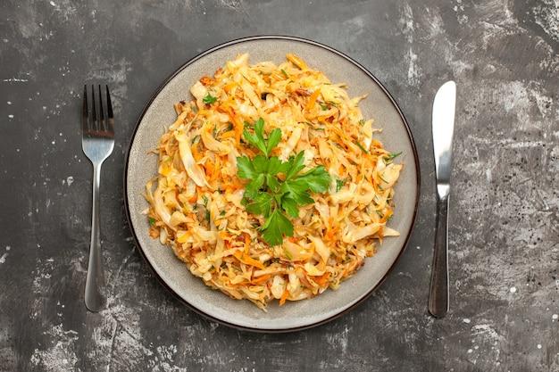 Bovenaanzicht kool kool wortelen kruiden op de plaat tussen mes en vork