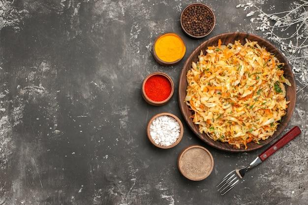 Bovenaanzicht kool met wortelen plaat van kool wortelen kruiden vork kommen met kruiden