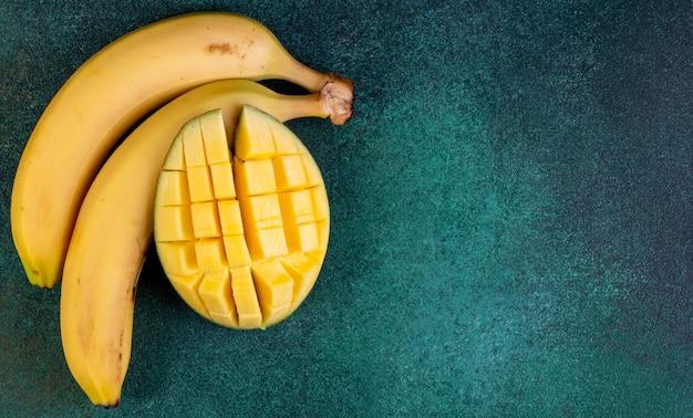 Bovenaanzicht kopie ruimte bananen met gehakte mango's op groen
