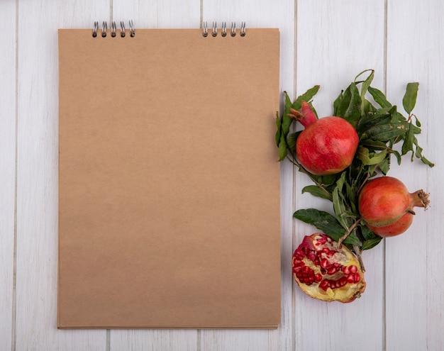 Bovenaanzicht kopie ruimte beige blocnote met granaatappels en tak met bladeren op witte achtergrond