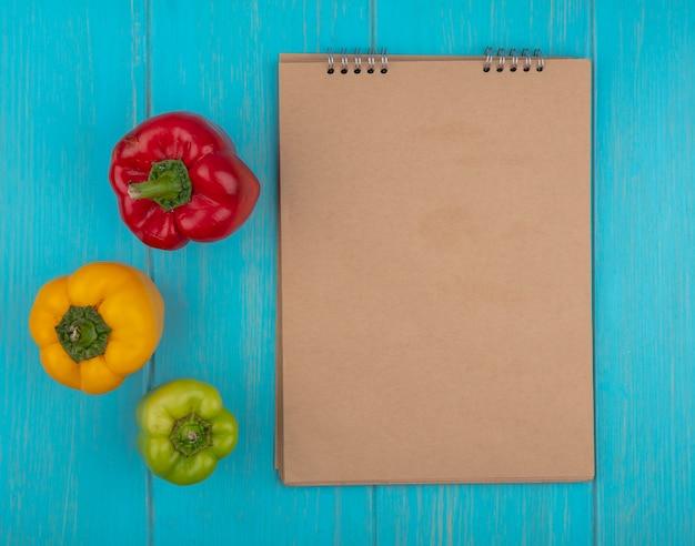 Bovenaanzicht kopie ruimte beige blocnote met paprika geelgroen en rood op turkooizen achtergrond
