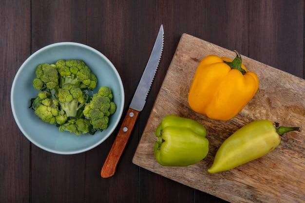Bovenaanzicht kopie ruimte broccoli in kom met groene paprika's en mes op snijplank op houten achtergrond
