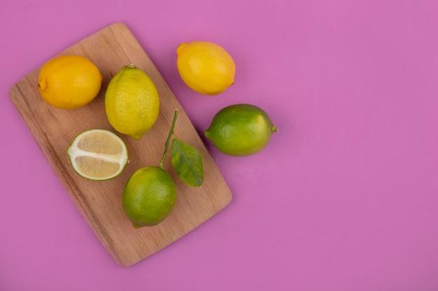 Bovenaanzicht kopie ruimte citroenen met limoenen op snijplank op roze achtergrond