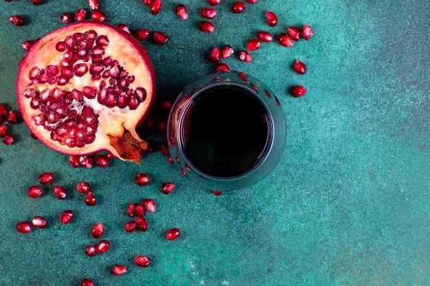 Bovenaanzicht kopie ruimte gehakte halve granaatappel met een glas granaatappelsap op een groene achtergrond