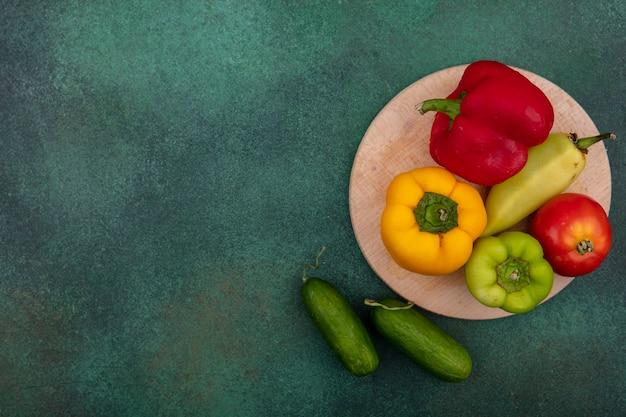 Bovenaanzicht kopie ruimte gekleurde paprika met tomaat op standaard en komkommers op groene achtergrond