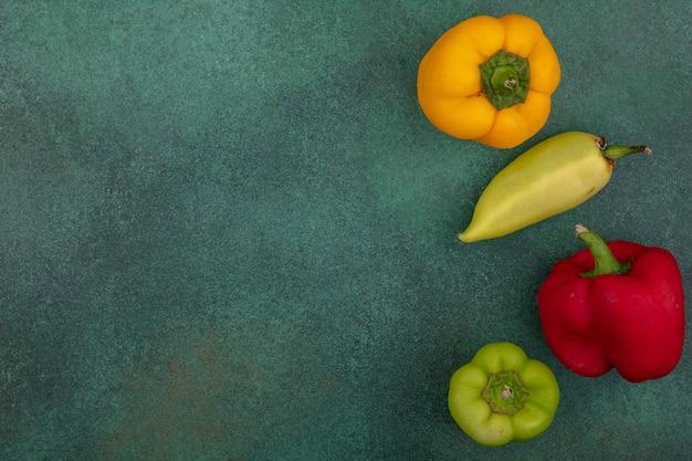 Bovenaanzicht kopie ruimte gekleurde paprika op een groene achtergrond