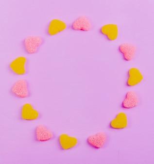 Bovenaanzicht kopie ruimte gele en roze marmelade in de vorm van een hart op een lichtroze achtergrond