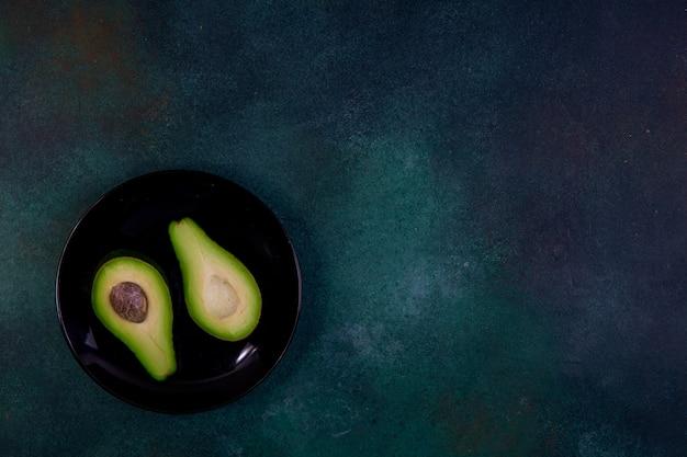 Bovenaanzicht kopie ruimte gesneden in halve avocado op een zwarte plaat op een donkergroene achtergrond