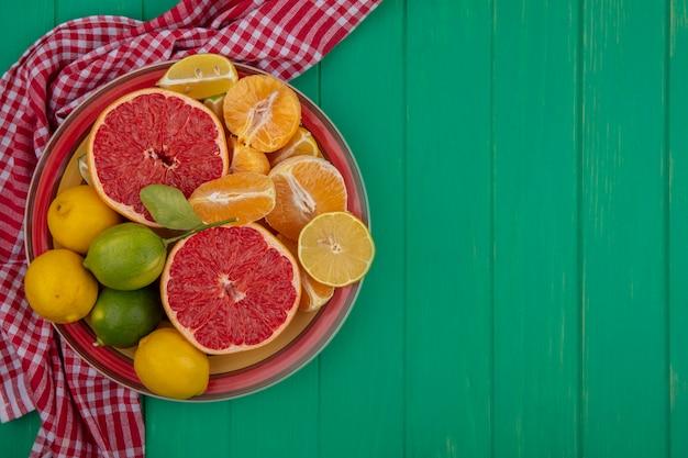 Bovenaanzicht kopie ruimte gesneden in halve grapefruit met gepelde sinaasappels en citroen met limoen op een bord op een rode geruite handdoek op een groene achtergrond