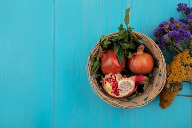 Bovenaanzicht kopie ruimte granaatappels in een mand met wilde bloemen op een turkooizen achtergrond