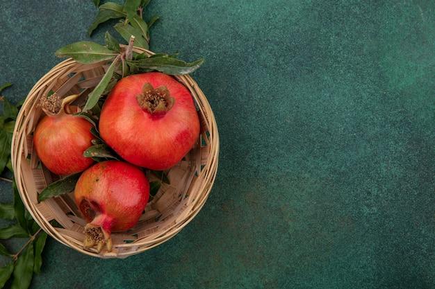 Bovenaanzicht kopie ruimte granaatappels met takken in een mand op een groene achtergrond