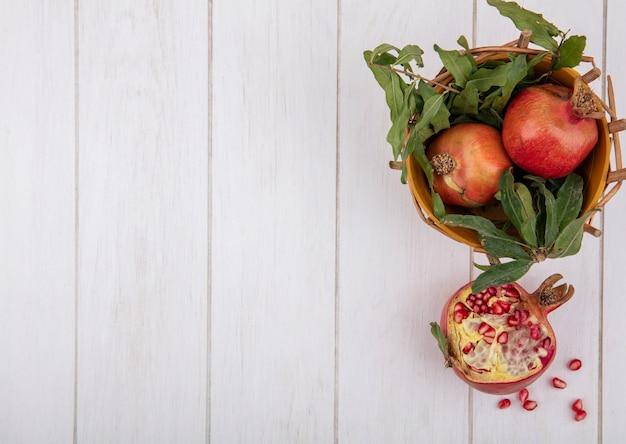 Bovenaanzicht kopie ruimte granaatappels met takken van bladeren in mand op witte achtergrond