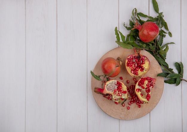 Bovenaanzicht kopie ruimte granaatappels op snijplank met takken van bladeren op witte achtergrond