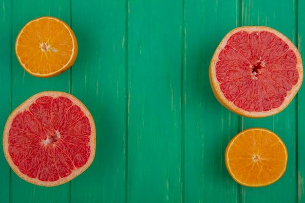 Bovenaanzicht kopie ruimte grapefruit helften met sinaasappelen op groene achtergrond