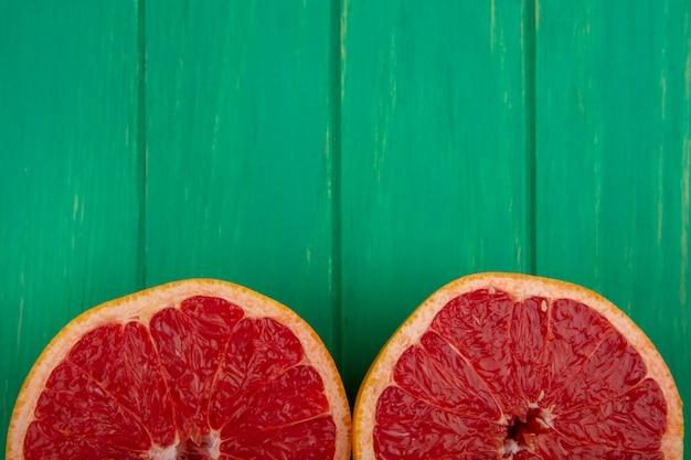 Bovenaanzicht kopie ruimte grapefruit helften op groene achtergrond